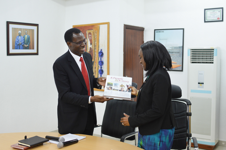 "Engr. Gbenga Adebayo presenty the CNSSL Coompany Book, ""A people & A Story"", to the Minister"
